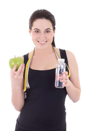 young beautiful sporty woman with bottle of water, apple and measuring tape isolated on white background photo