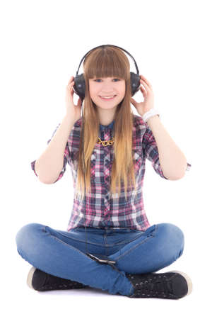 cute teenage girl sitting and listening music with headphones isolated on white background photo