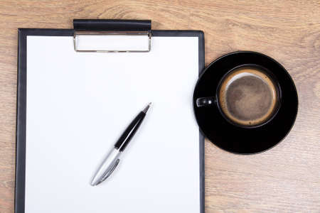 close up of blank clipboard, pen and cup of coffee on wooden table photo