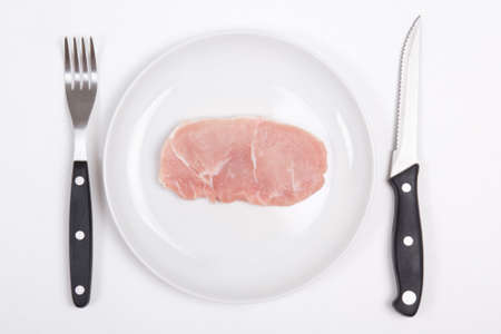 fresh raw pork chop on a white plate with fork and knife photo