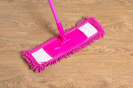 cleaning wooden floor with wet pink mop photo