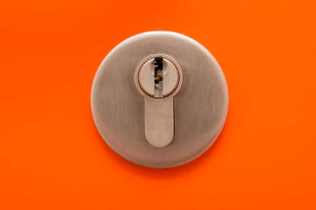 close up of keyhole on orange metal door photo