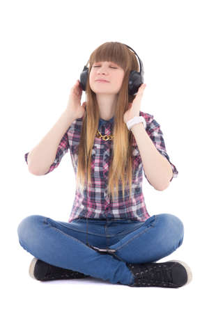 cute dreaming teenage girl sitting and listening music with headphones isolated on white background photo