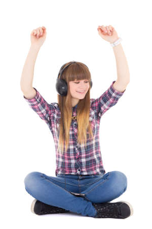 cute teenage girl  listening music in headphones and dancing isolated on white photo