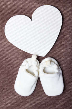 baby shoes and plastic heart over brown background photo
