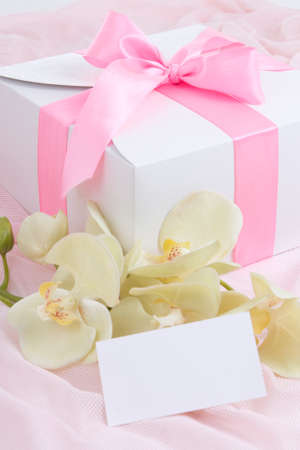 close up of gift box with pink ribbon, white orchid and blank card photo