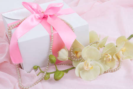 gift box with pink ribbon, orchid and pearl necklace over pink photo