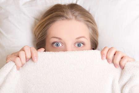 毛布の下のベッドで横になっている面白い若い美しい女性