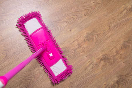 cleaning wooden parquet floor with wet pink mop photo