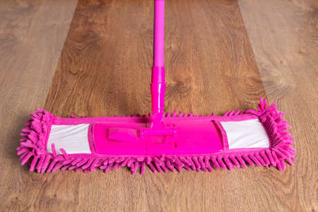 close up of pink cleaning mop on wooden parquet floor - before after photo