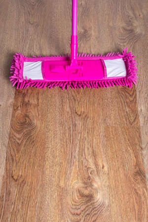 close up of wooden parquet floor with pink cleaning mop - before after photo