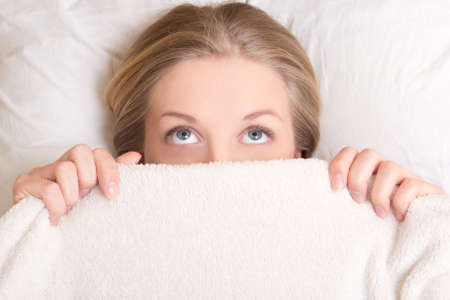 funny young beautiful woman lying in bed under blanket and dreaming Stock Photo
