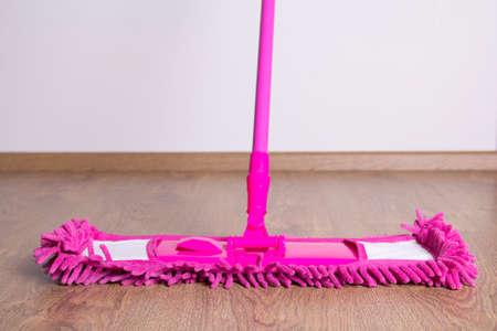 pink cleaning mop on wooden parquet floor