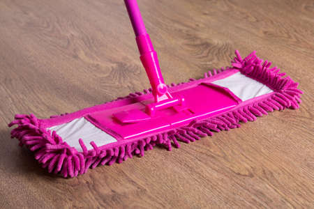 close up picture of wooden floor with pink cleaning mop photo