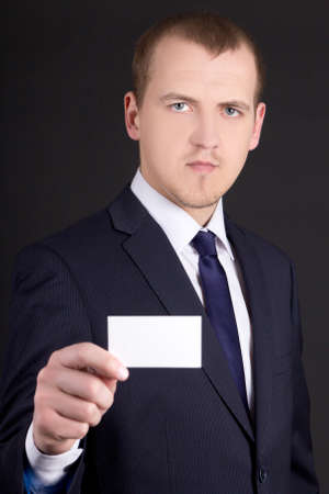 young business man in suit showing visiting card over grey background photo