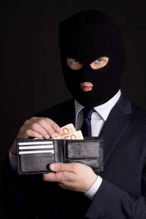 fraudster: man in business suit and black mask holding leather purse with euro banknotes Stock Photo