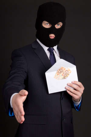 fraudster: bribery concept - man in suit and mask with money in white envelope ready to handshake