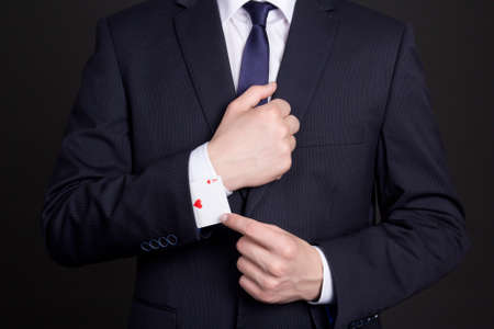 businessman with ace card hidden under suit sleeve photo