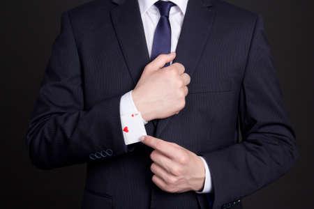 businessman with ace card hidden under suit sleeve Stock Photo