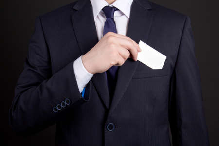 businessman holding blank visiting card out of his suit pocket photo