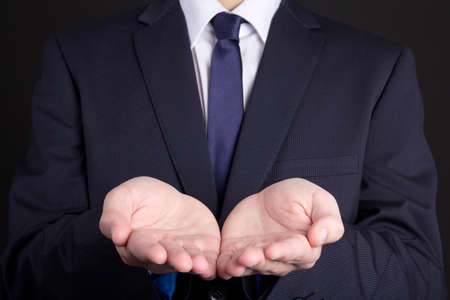 business man holding hand presenting product over dark background photo