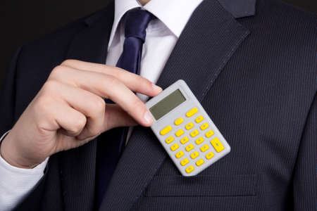 business man putting calculator into suit pocket photo