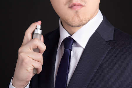 close up of handsome young business man using perfume photo