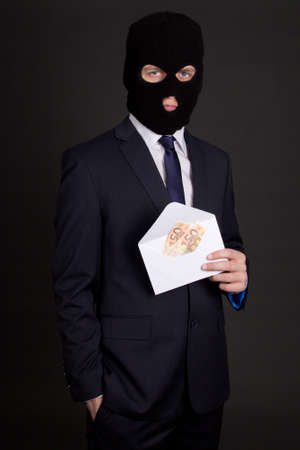 bribery: bribery concept - man in business suit and black mask holding envelope with money