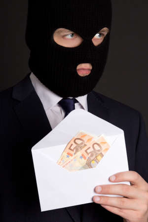 fraudster: bribery concept - masked man in suit holding white envelope with money