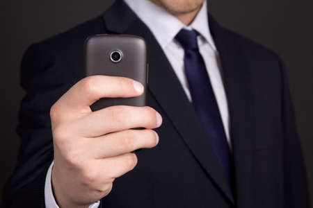 users video: modern mobile phone with camera in business man hand