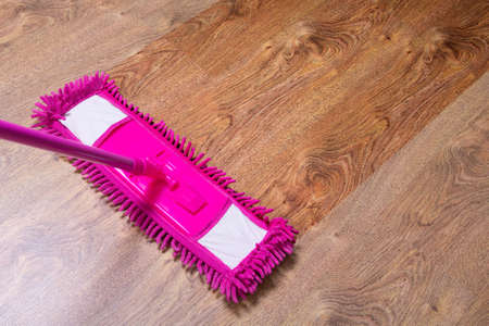 cleaning the parquet floor with wet pink mop -  before after Фото со стока