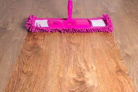close up of wooden floor with pink cleaning mop photo
