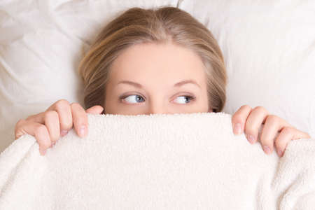 portrait of funny young beautiful woman lying in bed under blanket photo