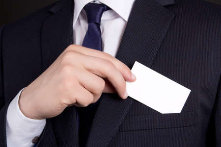 close up of businessman holding blank visiting card out of his suit pocket photo