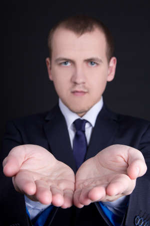 young business man presenting something on his hand over grey photo
