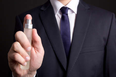 perfume spray: perfume bottle in young business man hand