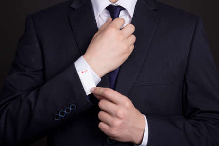 mans hand hiding ace in business suit sleeve