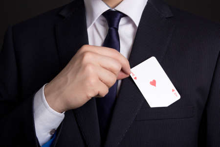 mans hand hiding playing card in business suit pocket Stock Photo