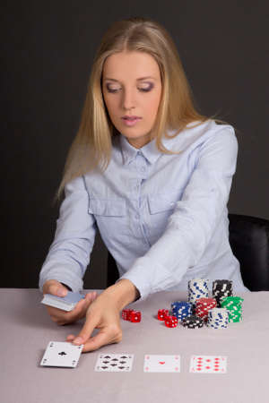young beautiful blond woman with playing cards and poker chips photo