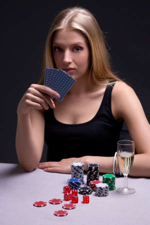 young beautiful blond woman playing poker in dark room photo