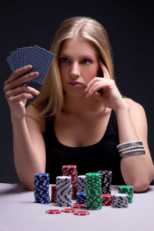 young beautiful serious woman playing poker in casino photo