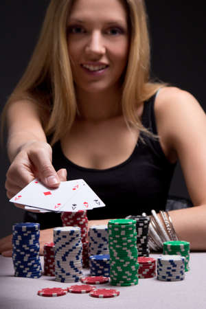 young blondie woman in casino with four aces in hand photo