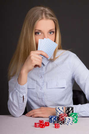 young attractive woman playing poker over grey background photo