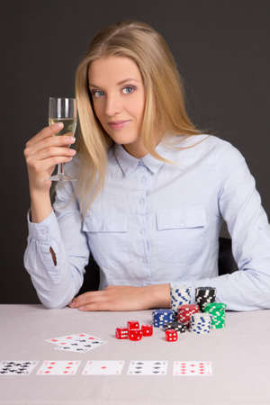 young beautiful blond woman with glass of champagne playing poker over grey background photo