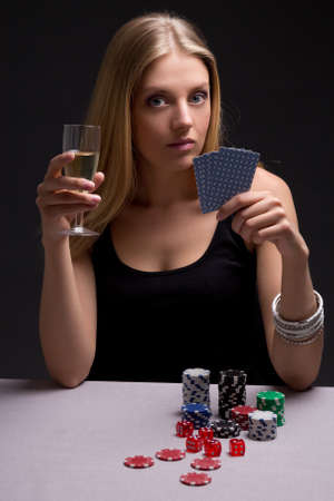 young beautiful blond woman with glass of champagne playing poker photo