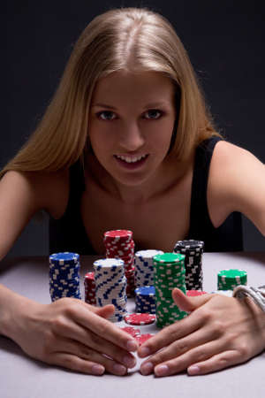 young beautiful blond woman with poker chips in casino photo