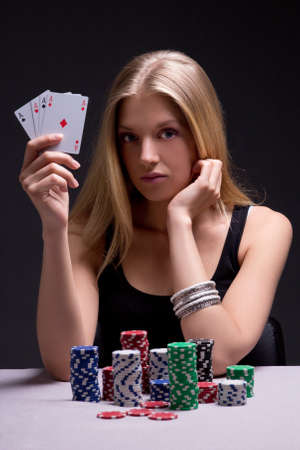 young woman in casino with cards and chips over grey background photo