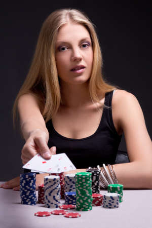young woman in casino showing four aces over grey photo