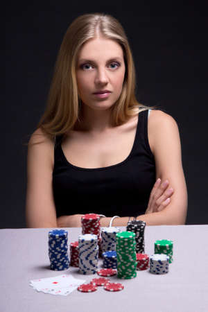 serious woman sitting in casino with cards and chips photo