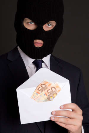 fraudster: bribery concept - masked man in business suit holding envelope with euro banknotes
